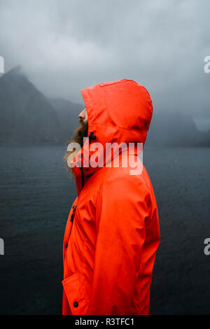 Norway, Lofoten, profile view of man with full beard at the coast - Stock Photo