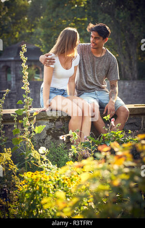 Romantic young couple sitting on wall in a park, with arms around - Stock Photo