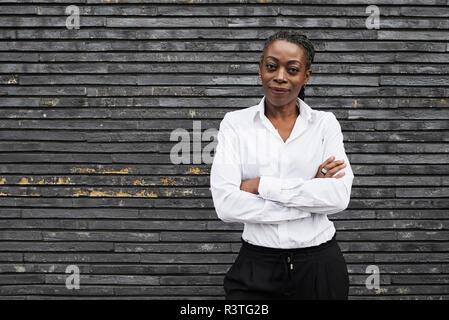 Portrait of smiling businesswoman  wearing white shirt - Stock Photo