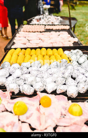 Corn cobs and potatoes wrapped in aluminum foil on a barbecue. - Stock Photo