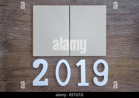 2019 study, work plan concept : Top view, flat lay with open empty note book on wood table with wooden cut number. Personal work space for New year re - Stock Photo