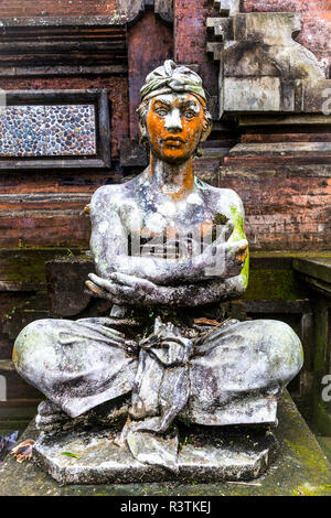 Verticle stone statue at Hindu Temple, Bali with crossed arms and legs. - Stock Photo