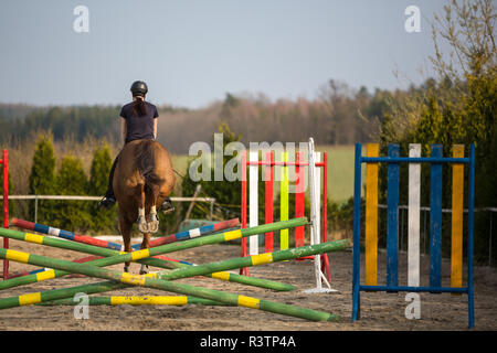 Young woman show jumping with horse - Stock Photo