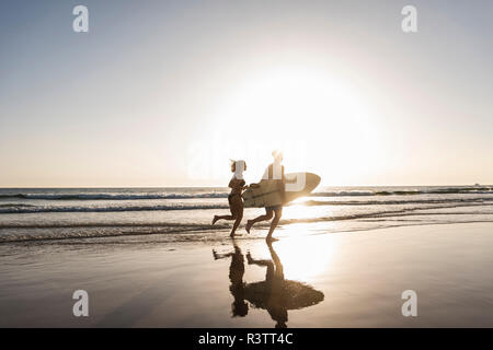 Young couple running on beach, carrying surfboard