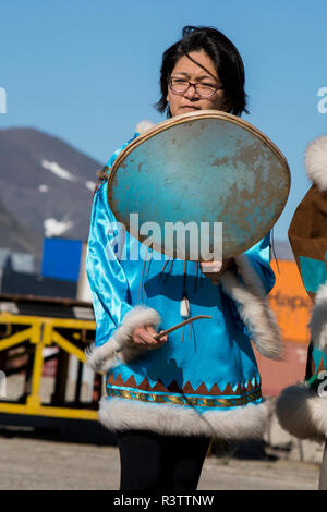 Russia, Komsomolskaya Bay, Chukotka Autonomous Okrug. Port of Provideniya. Native woman in traditional attire, drumming. - Stock Photo