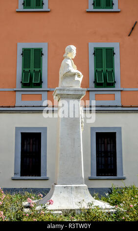 Classical marble statue on a plinth against a colourful salmon-coloured wall in Fivizzano, Tuscany, Italy. - Stock Photo