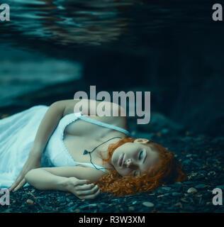 Young redhead beautiful woman lying underwater. - Stock Photo