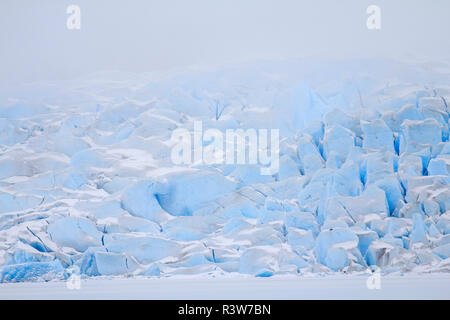 USA, Alaska. The face of the Mendenhall Glacier emerges from the clouds as it meets the frozen Mendenhall Lake. - Stock Photo