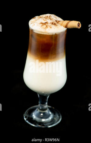 Alcoholic coffee cocktail with coffee liqueur, fresh cream and milk with isolated black background - Stock Photo