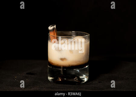 Flaming Cinnamon cocktail with kahlua, baileys irish cream and sambuca with isolated black background - Stock Photo