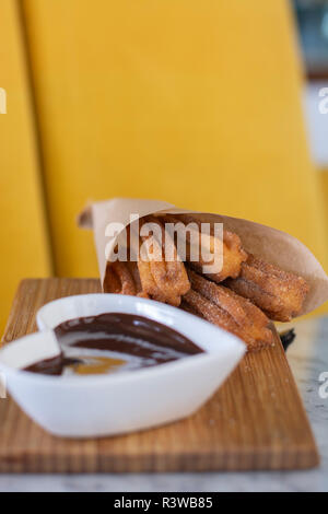 Churros fried pastry serve with hot chocolate sauce on wood - Stock Photo