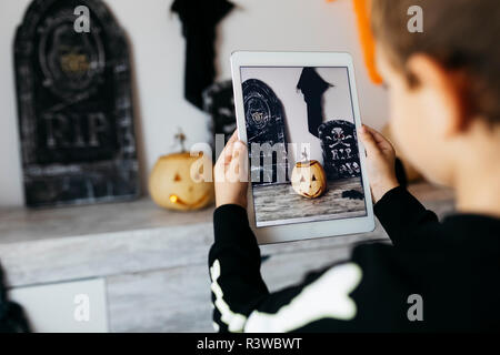 Little boy taking photo of Halloween decoration with digital tablet - Stock Photo