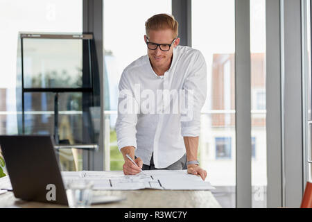 Smiling young man working on blueprint on desk in office - Stock Photo