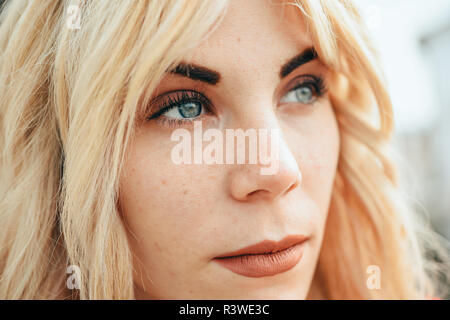 Close-up portrait of happy young blond woman sitting outdoors. Blonde girl with beautiful blue eyes. Stock Photo