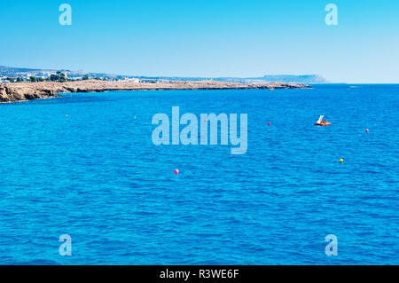 Image of calm sea surface near Agia Napa, Cyprus. One orange paddleboat in deep blue water against rocky coast and cape Greco on the background. Warm  - Stock Photo