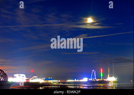 Moon and star trails at low tide over a brightly lit South Pier during Blackpool illuminations - Stock Photo