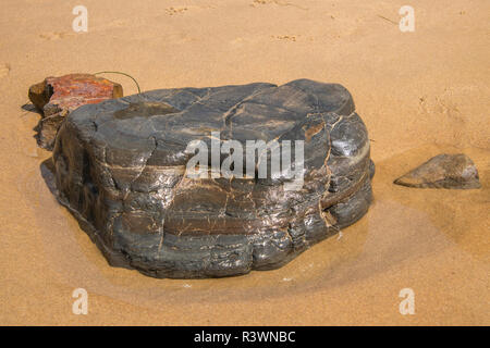 Wet large gray boulder and two other smaller rocks on a brown sand beach - Stock Photo