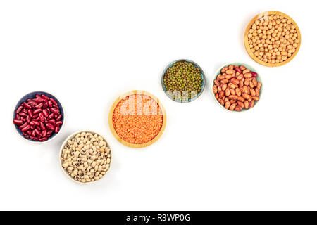 Legumes, shot from the top on a white background with copy space. Red kidney and pinto beans, lentils, chickpeas, soybeans, black eyed peas in bowls w - Stock Photo