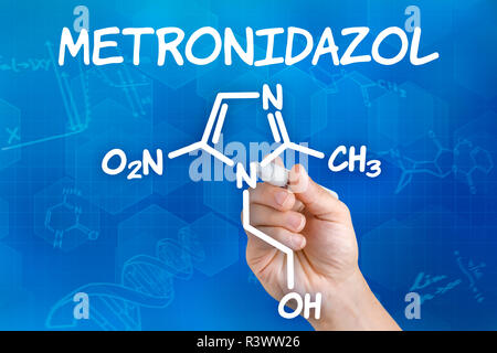 hand with pencil draws chemical structural formula of metronidazole - Stock Photo