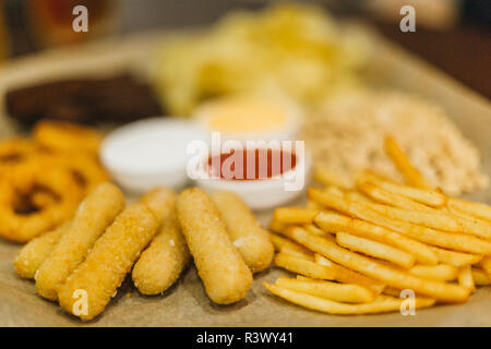 Lager beer and snacks on wooden table. Nuts, chips, peanut, toast, crackers. Appetizer fast food. Craft beer. Beerboard. Tomato cheese and garlic sauc - Stock Photo