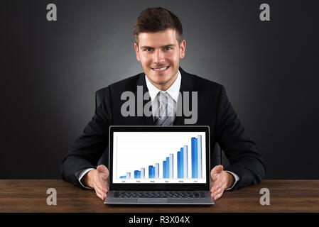 Businessman Showing Graph On Laptop - Stock Photo