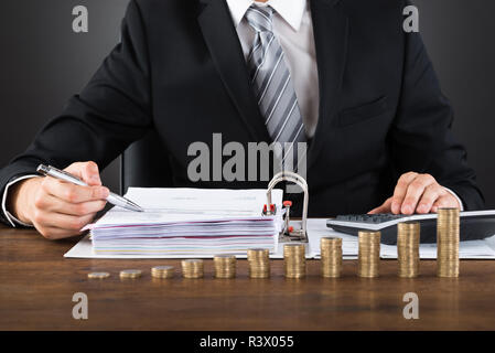 Businessman Calculating Invoice With Coins At Desk - Stock Photo