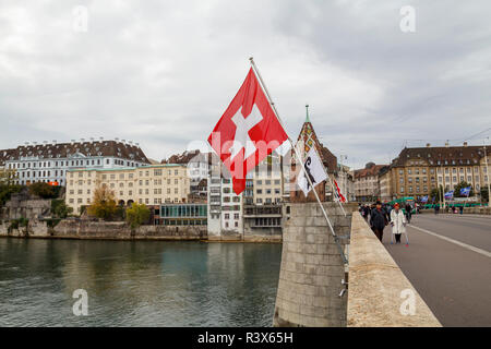 Middle bridge over the river Rhine in Basel, with hanging swiss flags - Stock Photo