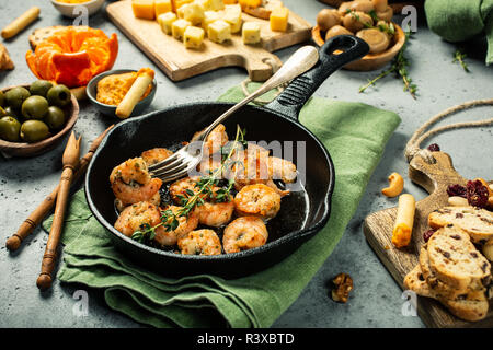 Shrimps roasted on frying cast iron pan - Stock Photo