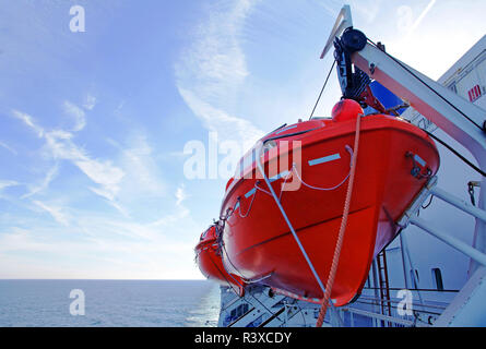 red lifeboats on a ship. rescue boats on a ferry - Stock Photo
