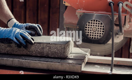 Workman using an angle grinder to cut a concrete block in a side view of his hands and the power tool, retro effect faded look. - Stock Photo