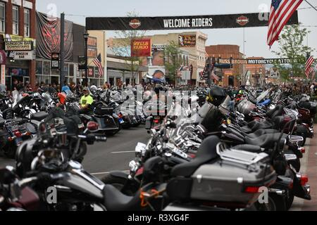 Motorcycle riders and motorcycles celebrating on Main Street during the worlds largest motorcycle rally in Sturgis, South Dakota, USA. - Stock Photo