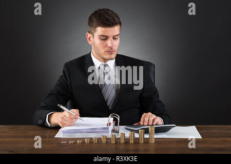 Businessman Calculating Tax With Coins At Desk - Stock Photo