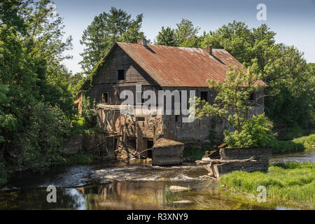 Ancient abandoned water mill surrounded by beautiful nature. House built of stone and wood, exterior walls and dilapidated bridge on river is reflecti - Stock Photo