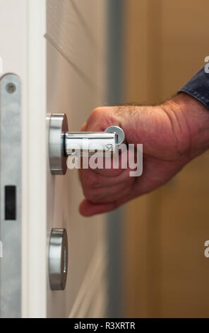 Door with an hand on the handle - Stock Photo