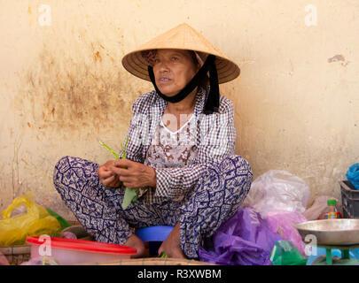 elderly woman selling vegetables on street market, Hoi An, Vietnam. - Stock Photo