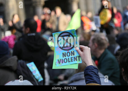 Manchester, UK. 24th Nov 2018. A leaflet of the Extinction rebellion symbol and words 'non Violent'  is held up as climate protesters march through city streets, Manchester, UK, 24th November 2018 Credit: Barbara Cook/Alamy Live News - Stock Photo