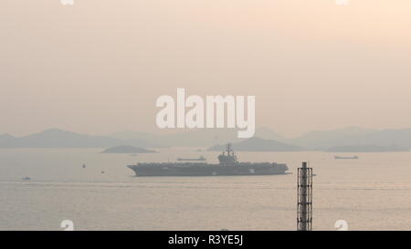 Hong Kong. 24th November 2018. The image represents the aircraft carrier USS Ronald Reagan (CVN 76) anchored near south of the Tsing Yi island in Hong Kong, with some smaller boats near her, the image was shot during sunset on 24 November 2018. Credit: Chun Kit Li/Alamy Live News - Stock Photo