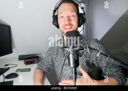 Young male behind condenser microphone radio podcast host voice recording - Stock Photo