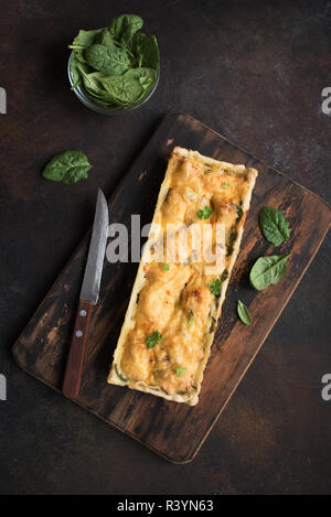 Salmon Spinach Pie (quiche) with cheese on dark rustic background. Homemade salmon tart for healthy lunch, top view, copy space. - Stock Photo