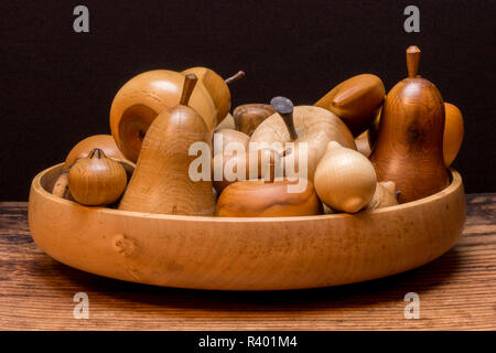 Handmade carved wooden fruit on a wooden table with a black background - Stock Photo