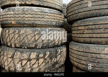 Stacks of used worn muddy black rubber tires and assorted tread wear patterns. - Stock Photo
