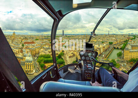 Helicopter cockpit flying on Notre Dame skyline of Paris, French capital, Europe. Scenic flight over Paris cityscape. - Stock Photo