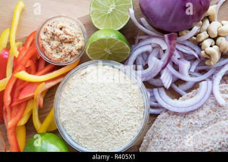 Nutritional yeast surrounded by other fresh ingredients for creamy vegan peppers and onions. - Stock Photo