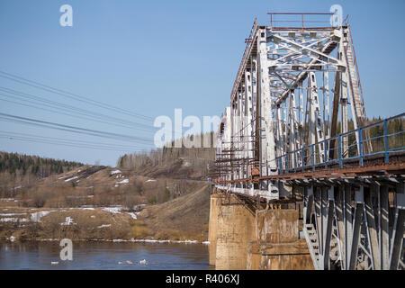 railway crossing over the bridge close-up over the river - Stock Photo