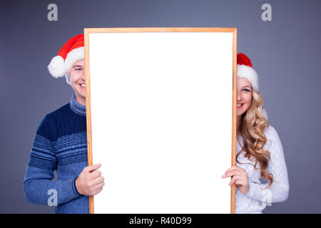 Christmas couple holding white board with empty copy space - Stock Photo