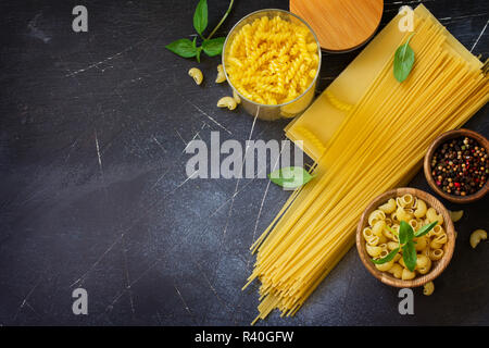 Various pasta. Ingredients for cooking pasta on a stone table. Top view flat lay background. Copy space. - Stock Photo