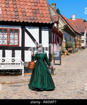 Woman dressed in period costume in The Old Town (Den Gamle By), an open air museum in Aarhus, Denmark - Stock Photo