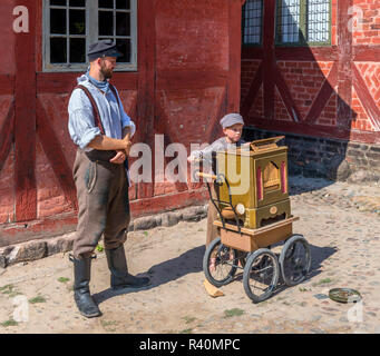 Man and young boy in period costume playing barrel organ, Market Square (Torvet), The Old Town (Den Gamle By), an open air museum in Aarhus, Denmark - Stock Photo