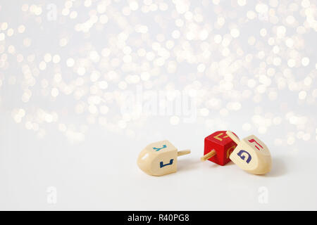 Happy Hanukkah greeting card, invitation Traditional Jewish Festival of lights holiday symbols. Wooden dreidel toys on white table. Festive glittering golden bokeh lights background. Empty space. - Stock Photo