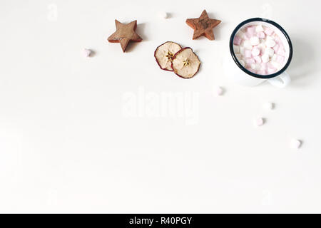 Christmas corner composition. Hot chocolate in enamel mug. Marshmallow,wooden stars, dry apple fruit slicess on white wooden table background. Winter breakfast. Flat lay, top view. Empty space. - Stock Photo
